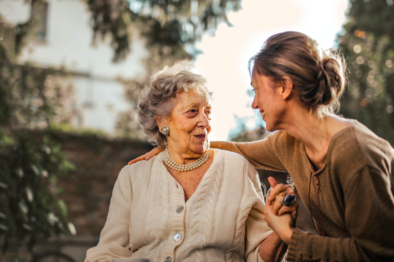 Une accueillante familiale discute avec une personne âgée, en la tenant par la main.