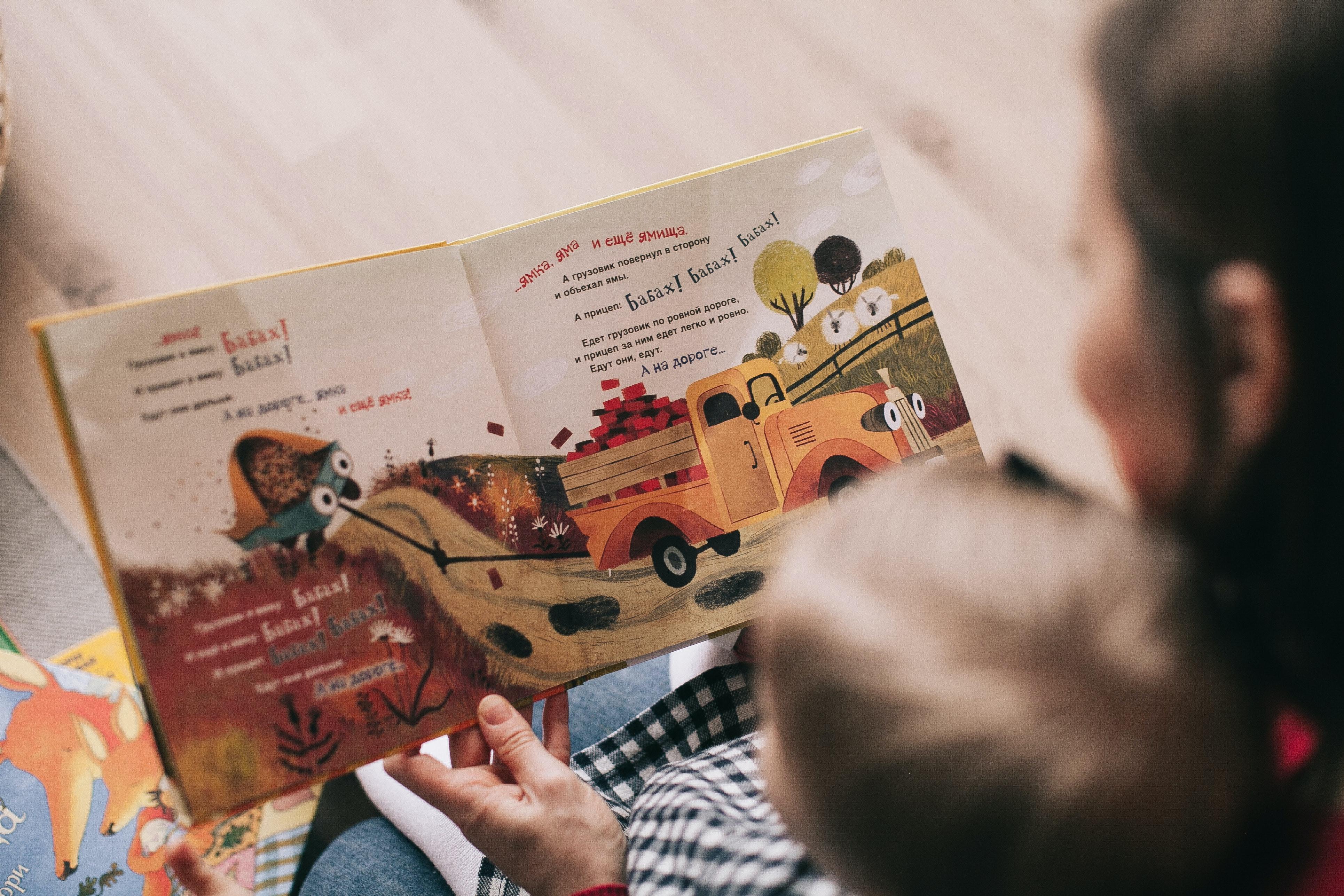 Une assistante maternelle fait la lecture à un bambin, assis sur ses genoux.