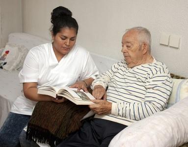 Une infirmière fait la lecture à un monsieur âgé. Ils sont assis dans un canapé blanc